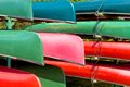 Colorful canoes partial images of bright green pink red and green stacked in the sun Stock Photos