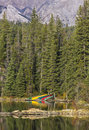 Colorful canoes reflect in lake a row of various colored a against pine trees and a mountain Stock Image