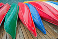 Colorful canoes several rest on dock Royalty Free Stock Photo