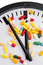 Colorful capsules on dial a clock symbolic photo for healthcare health reform congestion Stock Photos