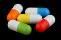 Colorful capsules medical on a black background Royalty Free Stock Photography