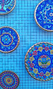 Colorful ceramic plates on a blue network wall Royalty Free Stock Photo
