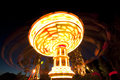 Colorful chain swing carousel in motion at amusement park at night. Royalty Free Stock Photo