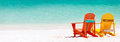 Colorful chairs on caribbean beach two wooden at tropical white sand in panorama with copy space perfect for banners Royalty Free Stock Photos