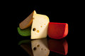 Colorful cheese variation luxurious on black background leerdammer and various flavoured gouda on black background with reflection Royalty Free Stock Image