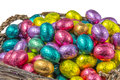 Colorful chocolate easter eggs in a basket wrapped aluminum foil isolated on white background Stock Image