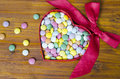 Colorful chocolate pills in a heart shaped box Royalty Free Stock Photo