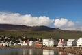 Colorful coastal houses near green mountain and water, Iceland, Akureyri Royalty Free Stock Photo