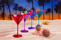 Colorful cocktail in a row cherry on sand palm trees with beach sunset Royalty Free Stock Image