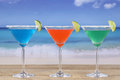 Colorful cocktails in martini glasses on the beach while vacation Stock Photography