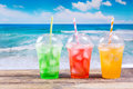 Colorful cold drinks in plastic cups on the beach Royalty Free Stock Photo
