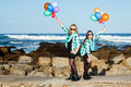 Colorful companions two caucasian friends dressed in matching clothing holding balloons in the air with the ocean in the Stock Photography