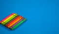 Colorful crayons lined on blue background. Royalty Free Stock Photo