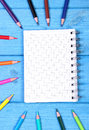 Colorful crayons and notepad on blue boards, school accessories, copy space for text Royalty Free Stock Photo
