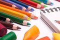 Colorful crayons and pencils many scattered on a white paper sheets Royalty Free Stock Image