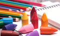 Colorful crayons and pencils many scattered on a white paper sheets Stock Images