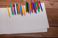 Colorful crayons with a white blank sheet of paper on a wooden b Royalty Free Stock Photo