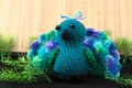 Colorful crocheted toy peacock a handcrafted from blue and green shades of yarn Royalty Free Stock Photography