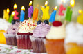 Colorful cupcakes with cream and fresh berries with burning candles Royalty Free Stock Photo