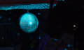Colorful disco ball in a nightclub turquoise blue mirrored metallic hanging the darkness with copyspace Royalty Free Stock Photography