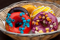 Colorful donuts different flavour closeup shot of fresh baked glazed of flavors served in a wicker bowl Stock Photo