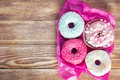 Colorful donuts on wooden background empty space for text