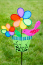 Colorful double pinwheel with bird on green grass Royalty Free Stock Photo