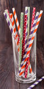 Colorful drinking striped straws in glass on a wooden table Royalty Free Stock Photo