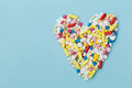 Colorful drug pills in shape of heart on blue background, pharmaceutical concept Royalty Free Stock Photo