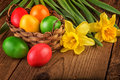 Colorful easter decoration with eggs in basket on dark wooden table