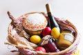 Colorful easter eggs in a basket with cake, red wine, hamon or jerky and dry smoked sausage on white background. Royalty Free Stock Photo