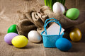 Colorful easter eggs on burlap and blue basket Royalty Free Stock Photography