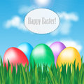 Colorful easter eggs on green grass blue sky background and frame for your text Stock Photo
