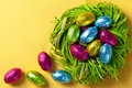Colorful easter eggs green nest holiday composition yellow paper background top view Stock Photo