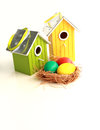 Colorful easter eggs in a nest with birdhouses on background bright yellow and green decorated ribbons white Royalty Free Stock Image