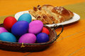 Colorful easter eggs and sponge cake on a table Stock Photos
