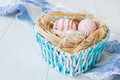 Colorful Easter Eggs on the white rustic wooden background with nest and blue basket on the linen towel Selective focus.
