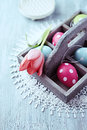 Colorful easter eggs in a wooden box close up of and tulip Stock Photo