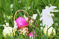 Colorful easter eggs, wooden rabbit and flowers on fresh spring grass in the garden.