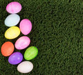 Colorful eggs for Easter holiday forming left hand border on gre