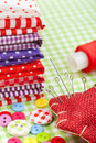 Colorful fabrics, buttons, pin cushion, thimble, spool of thread - set for sewing Royalty Free Stock Photo