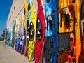 Colorful fiberglass kayaks on display outside sporting goods store