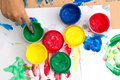 Colorful finger paints on a table with childrent hand Royalty Free Stock Photo