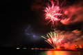 Colorful fireworks by the sea and lightning Royalty Free Stock Photos