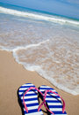 Colorful flip-flop sandals on sea beach Royalty Free Stock Photo