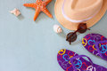 Colorful flip flops, starfish, shells, fedora hat and sunglasses on wooden background Royalty Free Stock Photo