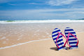 Colorful flipflop pair on sea beach Stock Photography