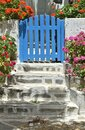 Colorful flowers by a blue garden gate on the secluded Greek island of Sikinos Royalty Free Stock Photo