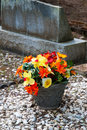 Colorful flowers outside tombstone in an ancient pioneer cemetery in the pacific northwest a pot of sets in memory of a lost one Stock Photos