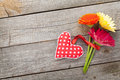 Colorful gerbera flowers and valentine s day heart toy on wooden background with copy space Stock Image